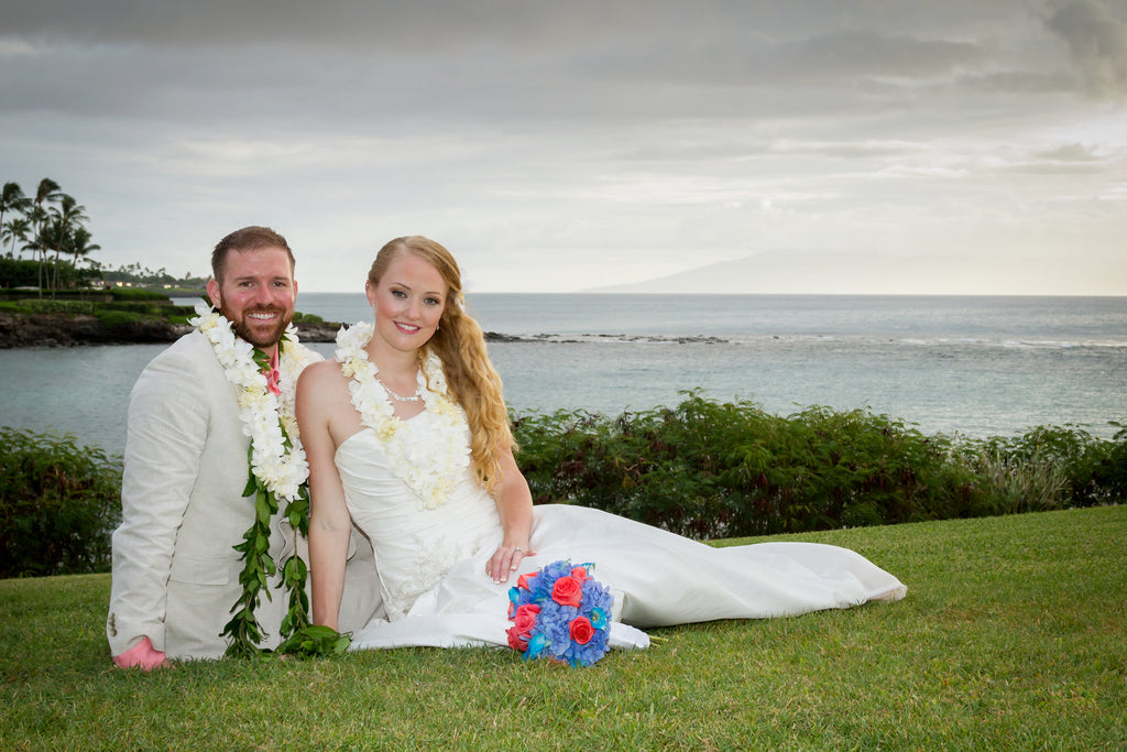 A Bride and Groom sit on a grassed area over looking the ocean
