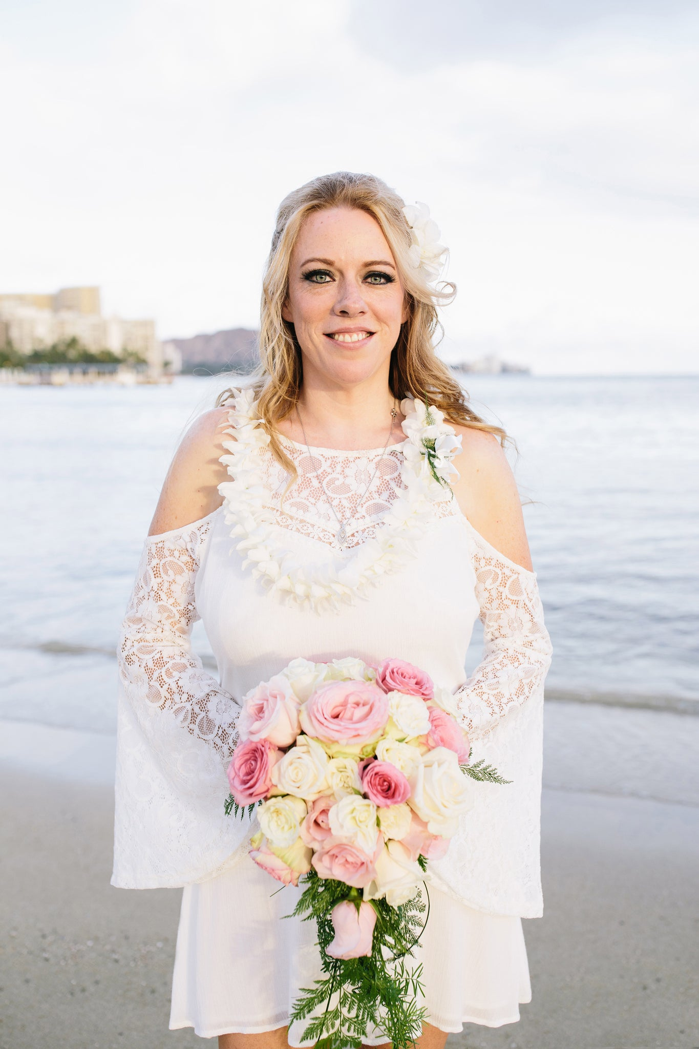 Bride poses with Rose Bouquet on Duke Kohanamoku Beach in Waikiki, Oahu, Hawaii