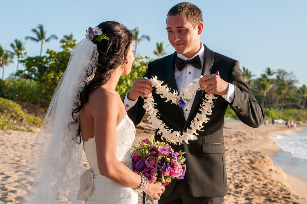 A Groom places a Hawaii Traditional Lei on his Bride