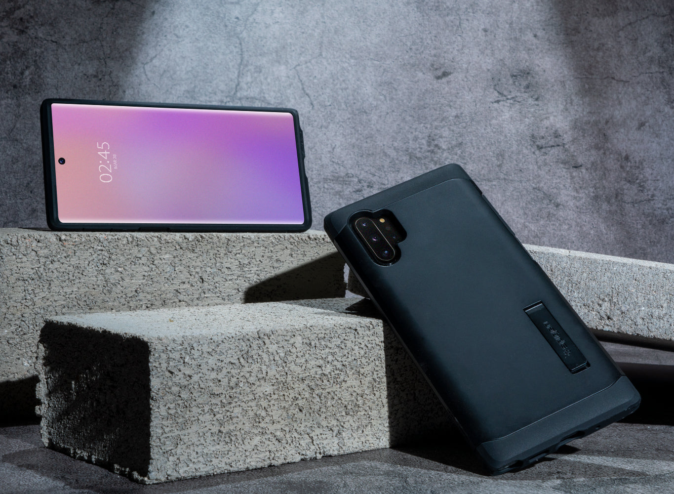 Two Galaxy Note 10 devices. The lower Note 10 device has the Tough Armor black case on it. The devices are propped up onto cement blocks.