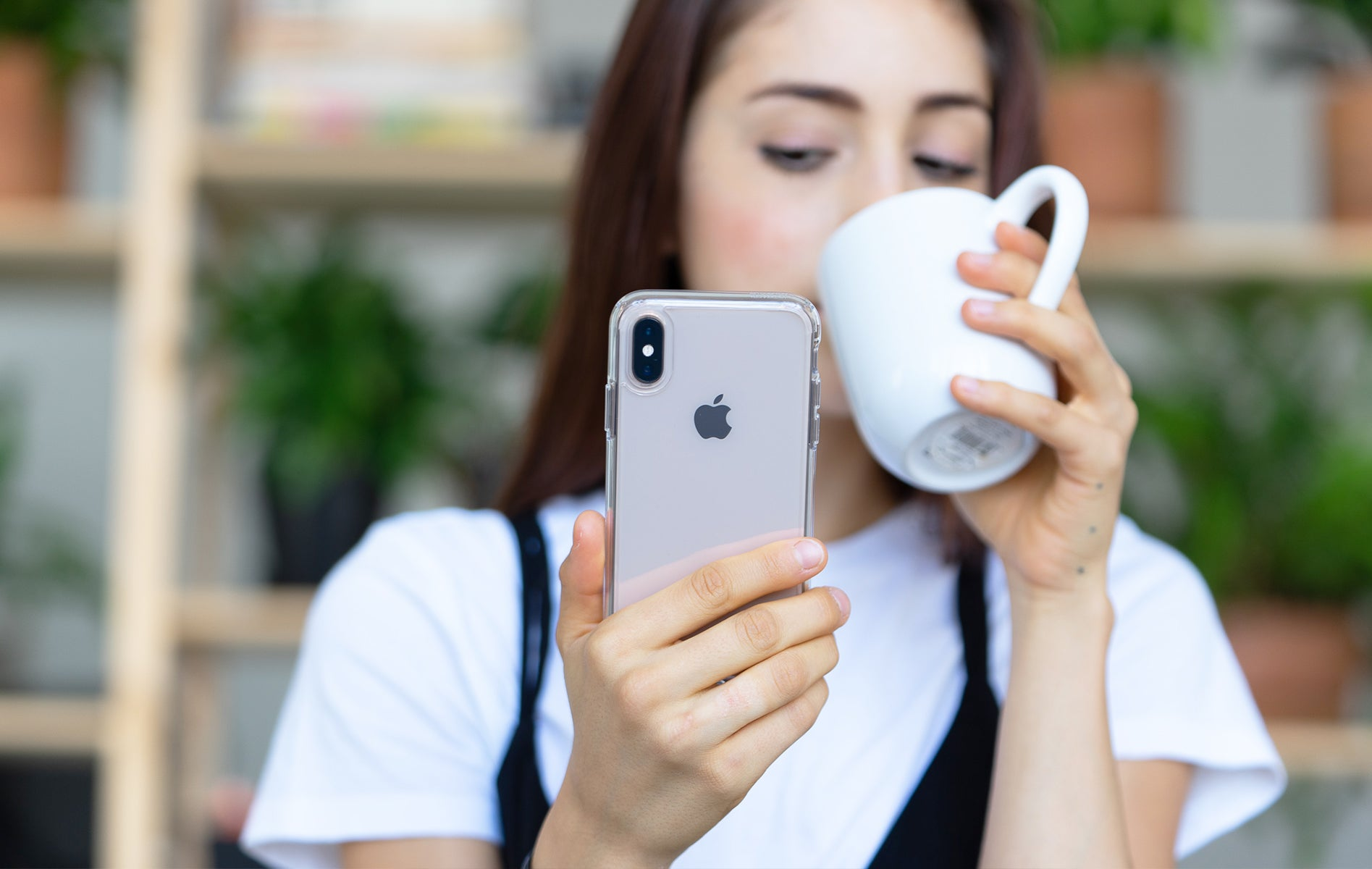 Woman holding a cup on one hand and an iPhone X with a clear case on the other.
