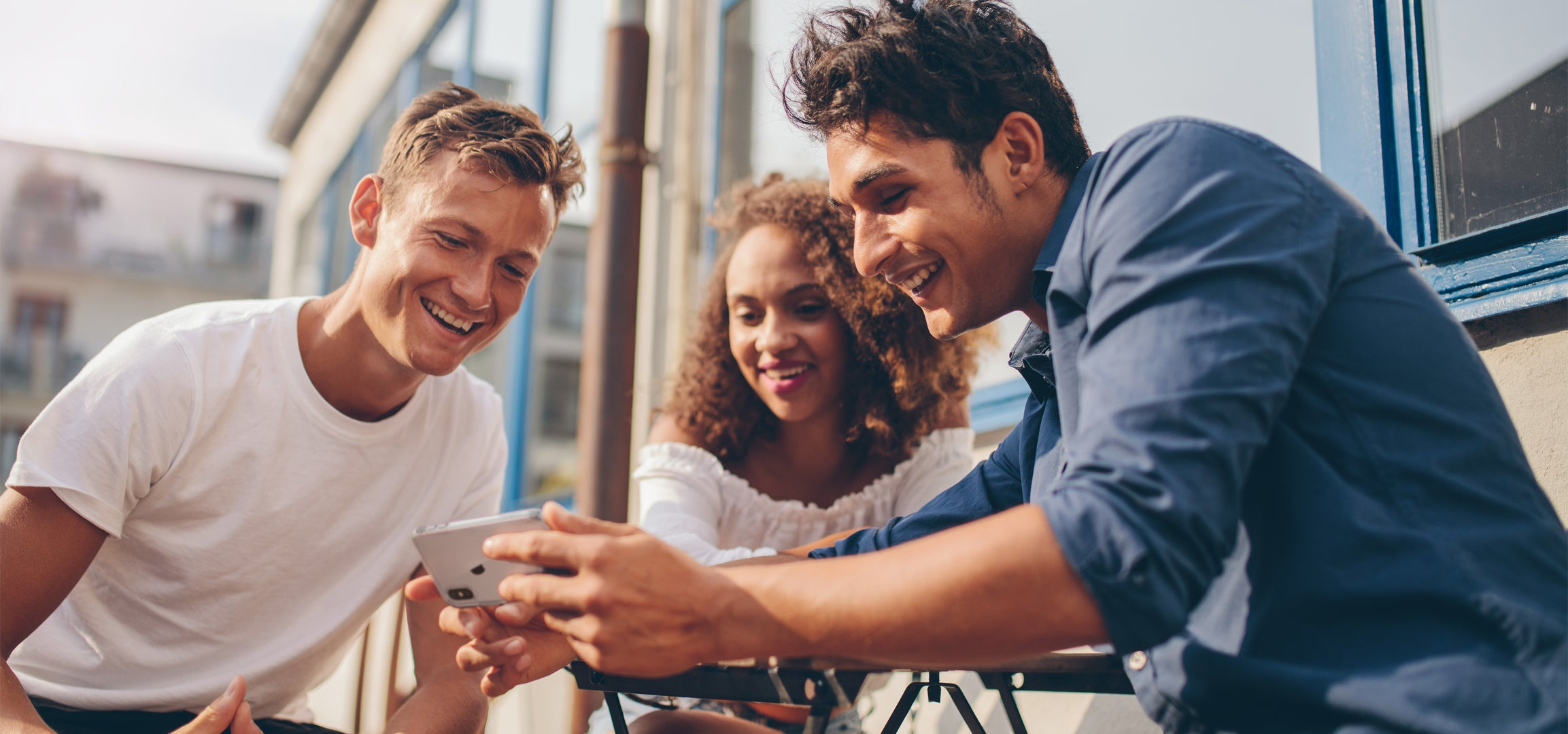 Three people looking at an iPhone with smiles