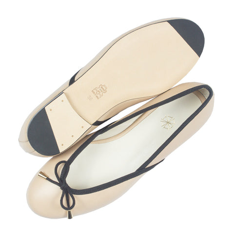 Shop online beige ballerina flats with contrast black trimming, calf leather uppers, lining and cow leather outsoles. Designed in Singapore and made in Spain. International shipping.