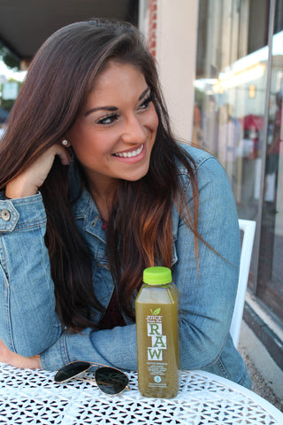miranda rodriguez sitting at table with juice from the raw bottle