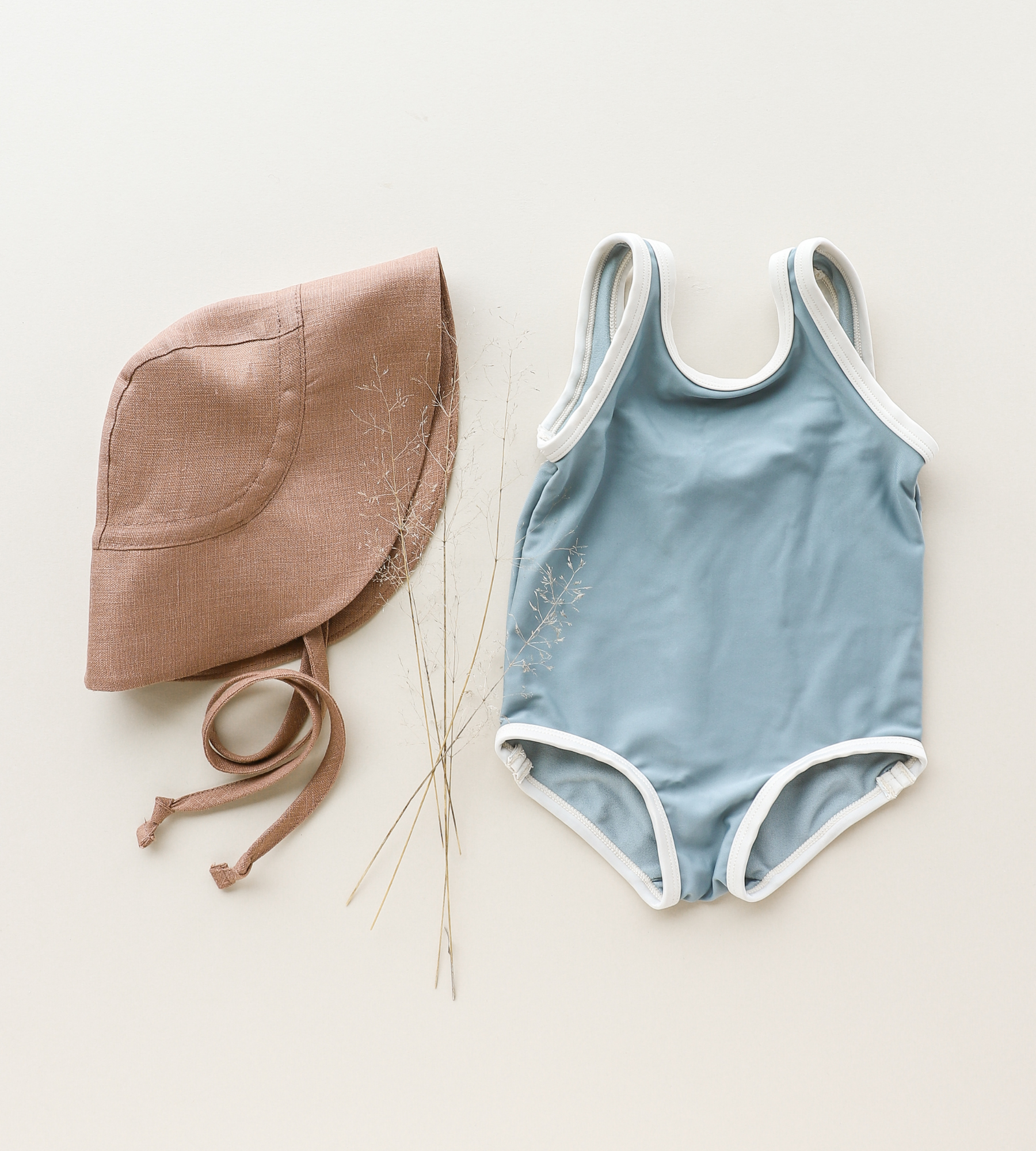 Caramel sunbonnet laid next to a light blue one-piece swimsuit with ivory trim