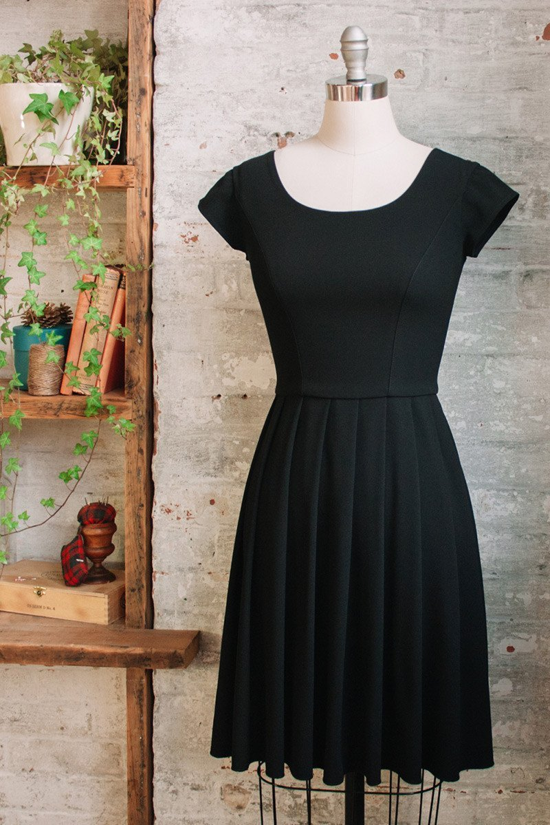 Knee length black pleated dress with cap sleeves in triacetate