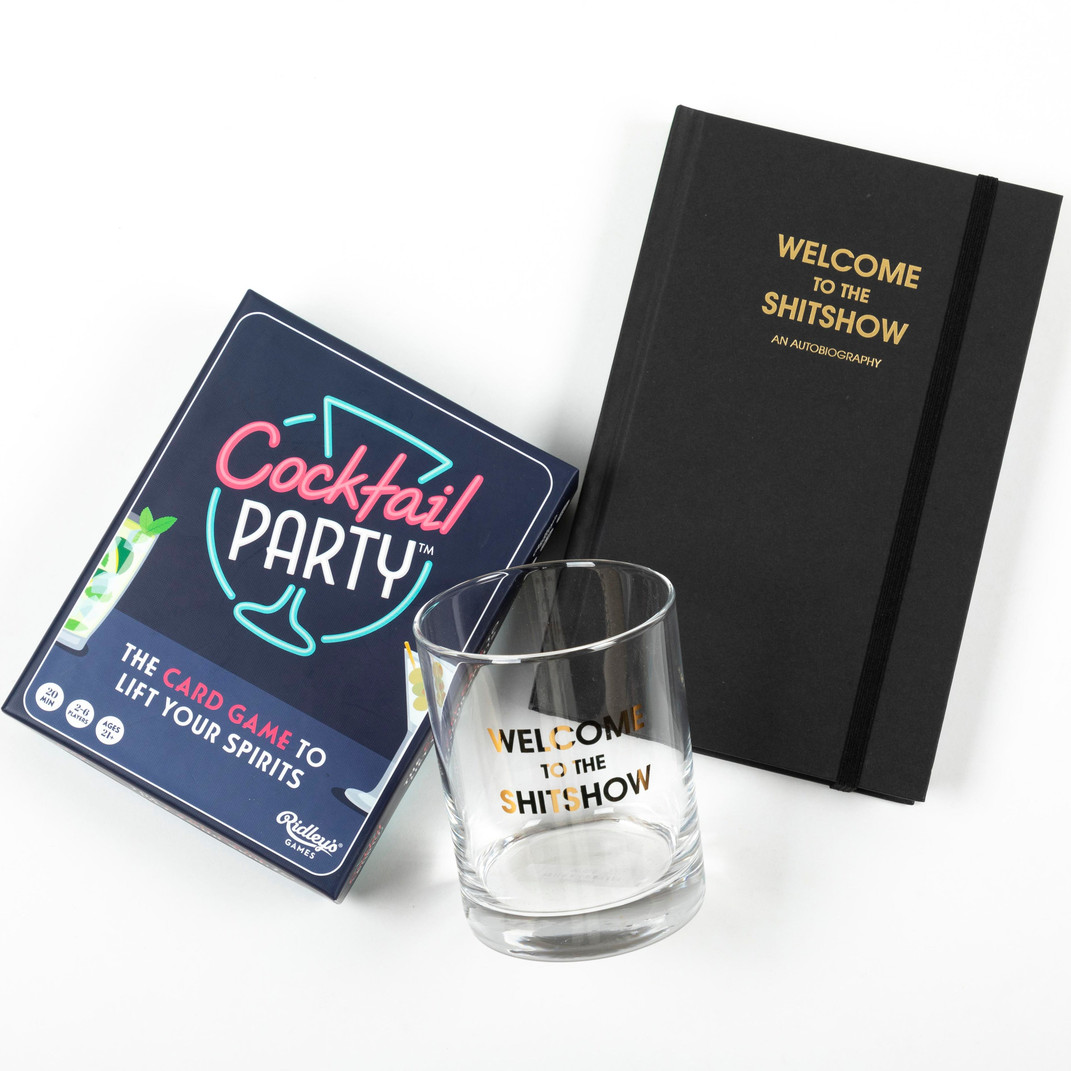 Welcome To The Shitshow gift set includes welcome to the shitshow gilt lettering rocks glass, journal and cocktail party card game.
