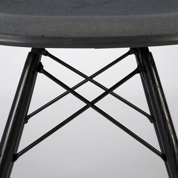 View of top of base of grey on black upholstered Eames DSW chair