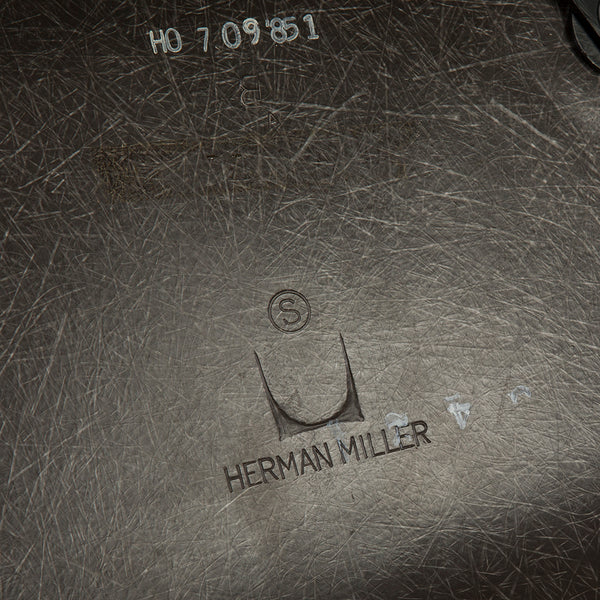 Close up view of logo on grey on black upholstered Eames DSW chair