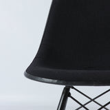 View of seat section of black on white upholstered Eames DSW chair