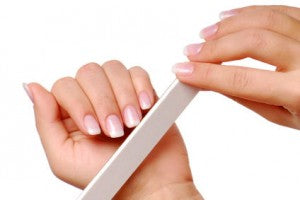 Body-care of hands. Woman polishing nails with thу nail file.