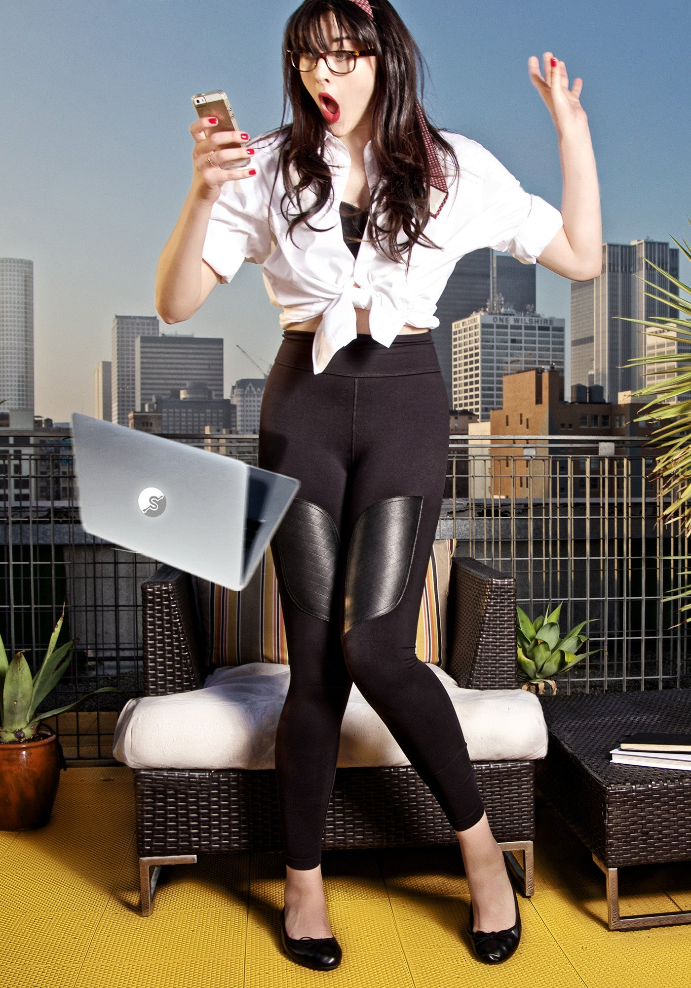 Working from home 2020. High waisted legging in black with foldover waistband, leather patches on thigh, convenient back pocket at waist. Made from premium high performance activewear fabric that wicks moisture away from your body to keep you comfortable. Downtown Los Angeles in background.