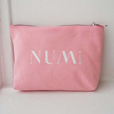 The Pouch from Numi, a pink cotton canvas bag with a zipper, placed on a windowsill