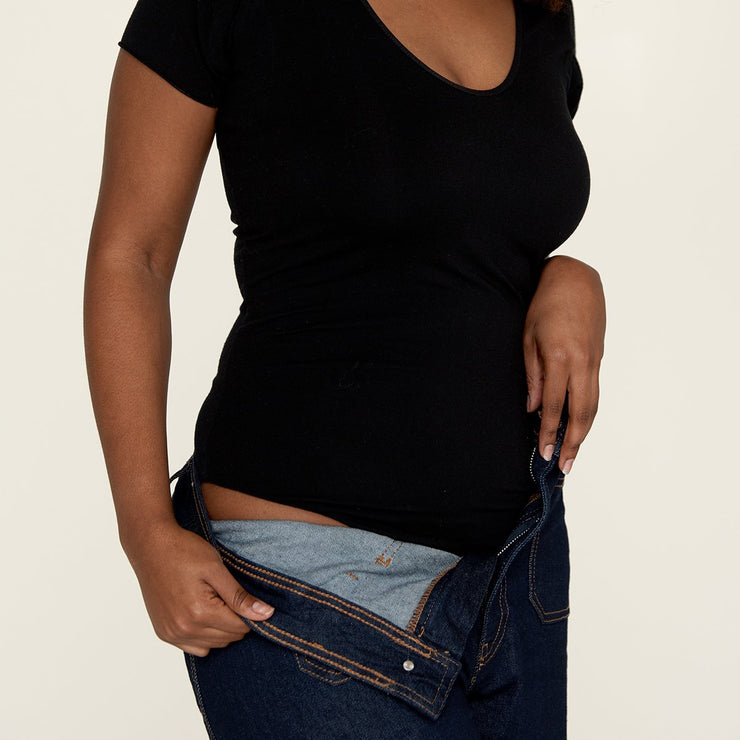 Woman putting on jeans, wearing The Bodysuit, a sweatproof undershirt from Numi in black