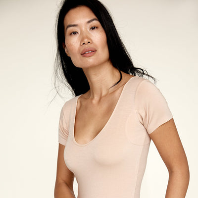 Woman wearing The Bodysuit, a sweatproof undershirt from Numi in light beige