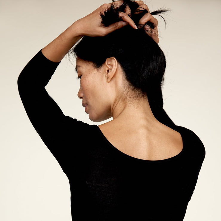 Woman holding her hair up, wearing The Three Quarter undershirt from Numi in black