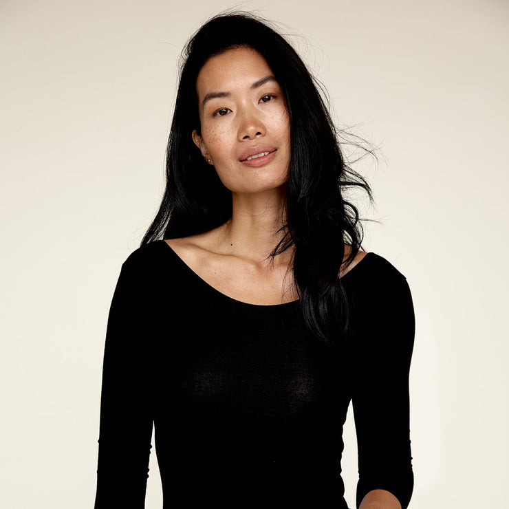 Woman wearing The Three Quarter undershirt from Numi in black, with the crew neck side