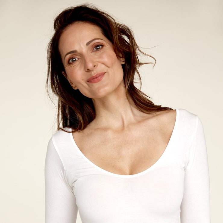 Woman smiling while wearing The Three Quarter undershirt from Numi in white