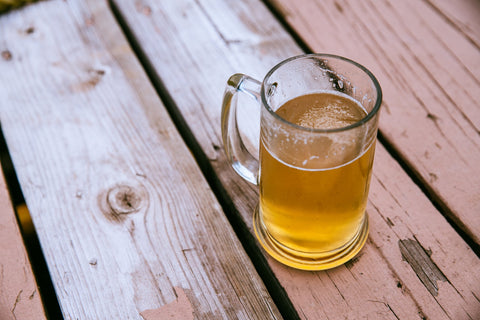 A photo of a mug of beer on a picnic table