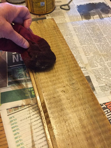 adding stain to wood board