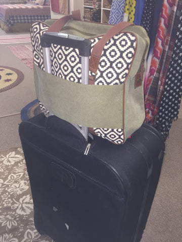 Wonderlust Tote shown with suitcase
