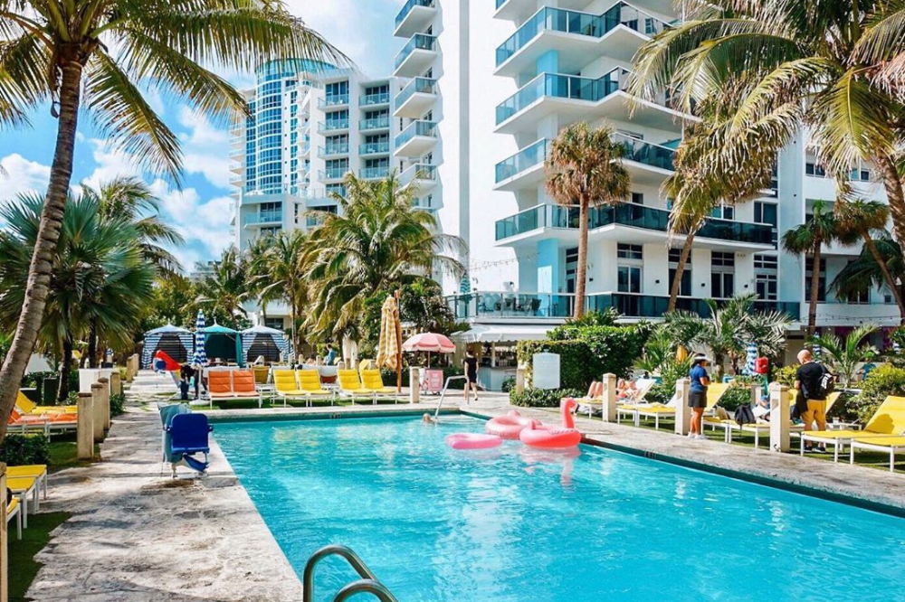 A beautiful pool with poolside seating shadowed by the fabulous Confidante Hotel in Miami.
