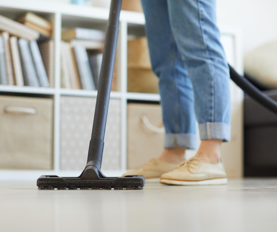 A person vacuuming the floor after bringing a cat into a new home.