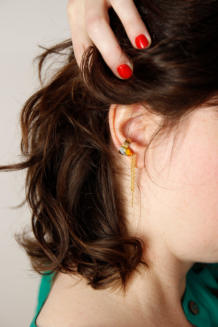 Woman wearing a unique Handcrafted Dangling Ear Cuff by Gré  with brass, gold chain and aquamarine