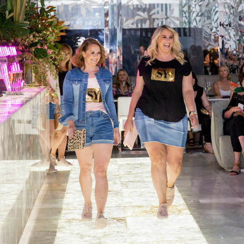 Bec and Jess wearing denim and Nikki sequin tees as they walk the catwalk