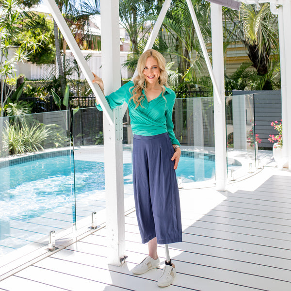 Lisa wearing our Cate technical shirt in green with our Maddy pants in Steel blue