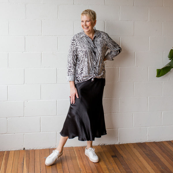 Susan wearing our Deborah satin skirt in black with our Sally safari button-up shirt and sneakers.