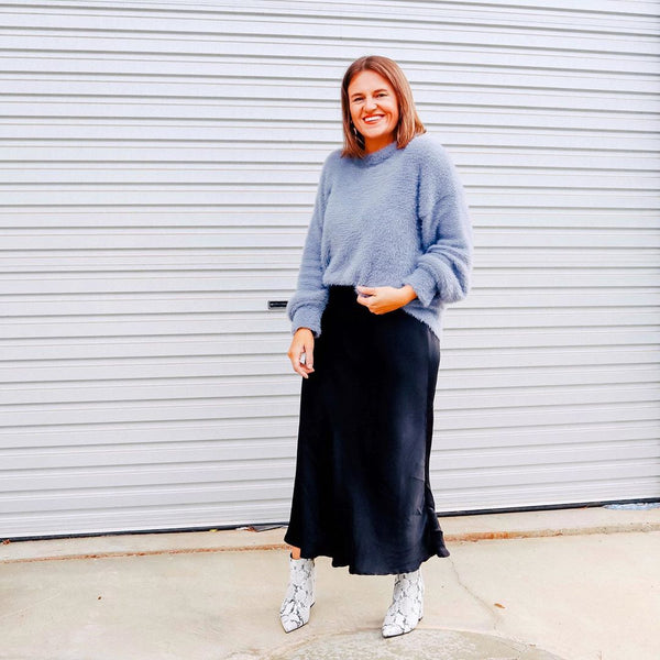 Jasmine wearing our Deborah black satin midi skirt with a blue knit