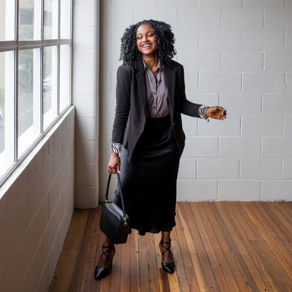 Sonia wearing our black Kerryn blazer with safari lining over our Cate technical shirt in sage and Deborah midi-skirt