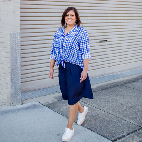 Jayanita wearing our gingham button up shirt and navy knee length skirt