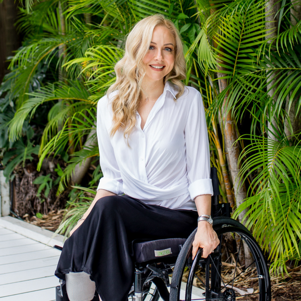Lisa our size 6 and 8 model wearing our Cate technical shirt in white sitting in her wheelchair