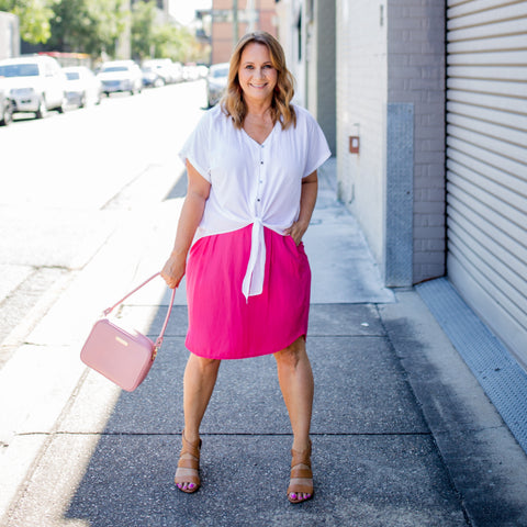 Karen wearing our Nicole blouse in white and Amanda skirt in Raspberry