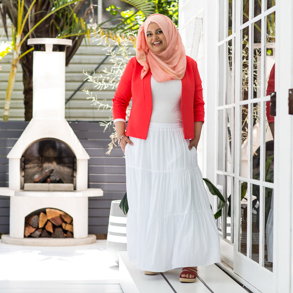 Faaiza in our Sophie technical skirt white and our Karen scuba jacket coral