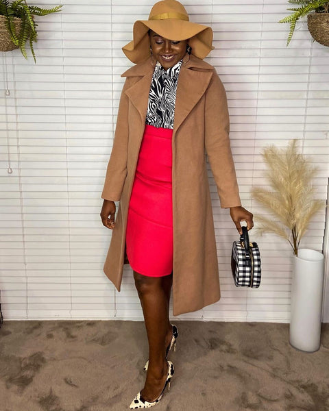 Sonia wearing styling you the label's Sally shirt with a bright pink high waisted skirt, camel coat and wide brim hat.