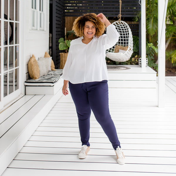 Asinate in our Suzie ponte jogger pant navy (Size 18) and our Felicity technical billow blouse white (Size 18)