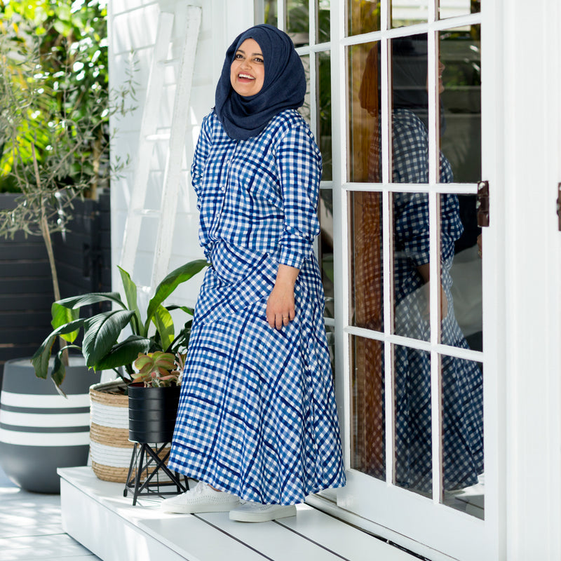 Faaiza wearing our Kimba shirt in gingham with our Ashlee midid skirt gingham paired with white sneakers