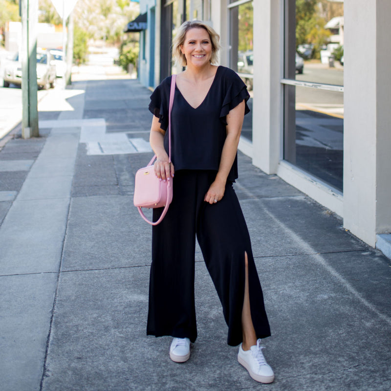 karen in our Barbara jumpsuit - black with a pink handbag and white sneakers