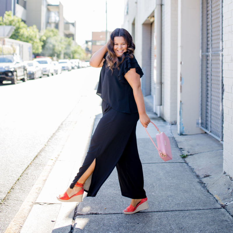Stacey in our Barbara jumpsuit - black with orange heels and a pink handbag
