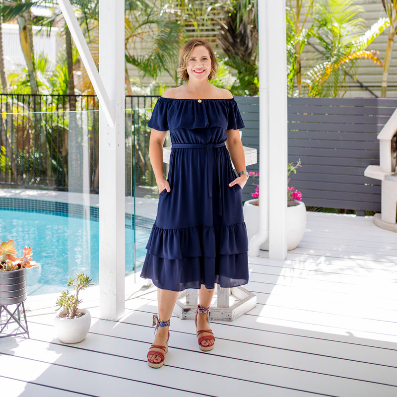 Bec wearing our natalie off-the-shoulder dress in navy with red heels.
