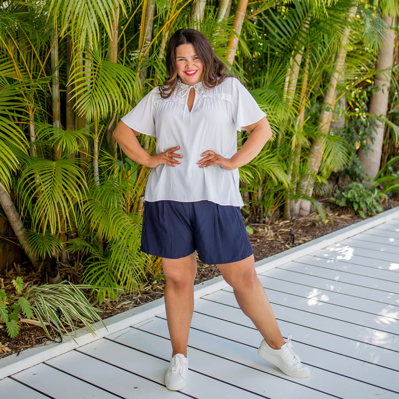 Stacey in our Kim technical blouse white and our Bec technical shorts in navy paired with white sneakers