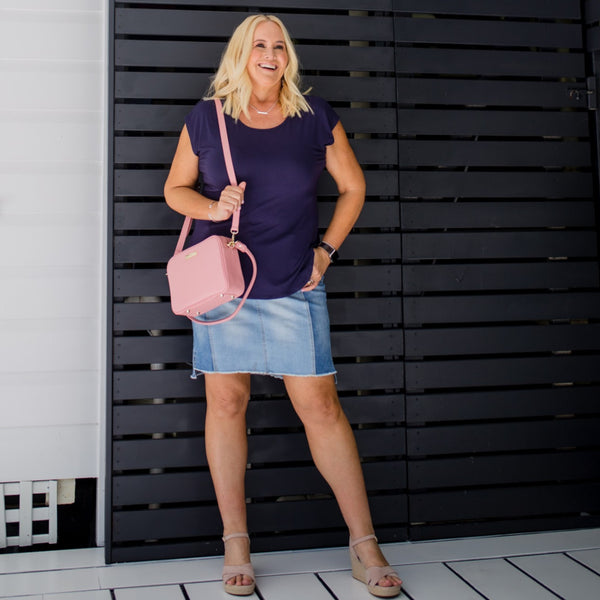 Nikki in our Beth skirt - denim with a navy tee, a pink handbag and nude heels