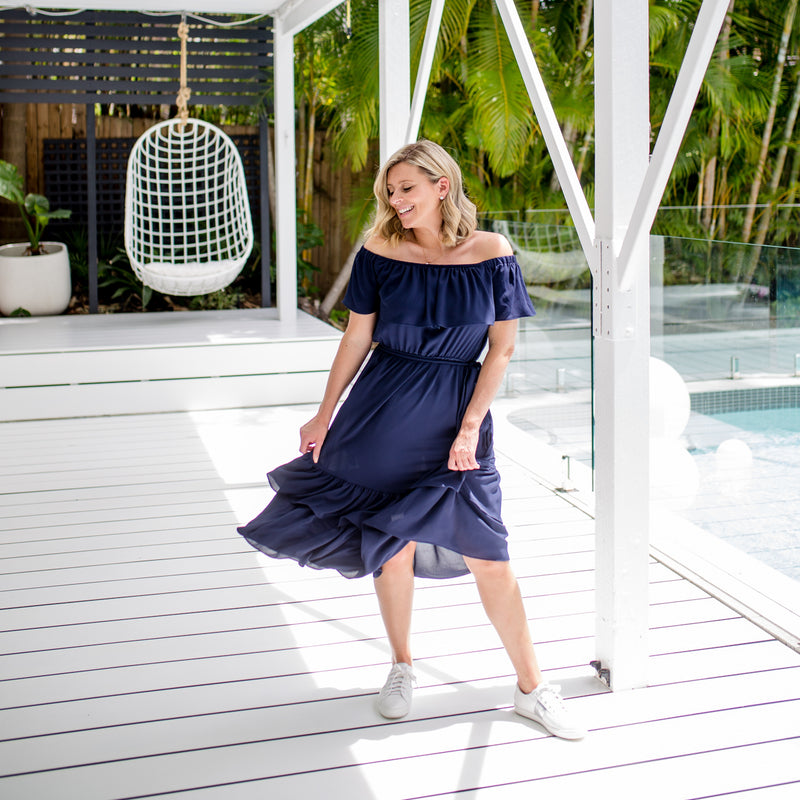 Brooke wearing our natalie off-the-shoulder dress in navy with white sneakers
