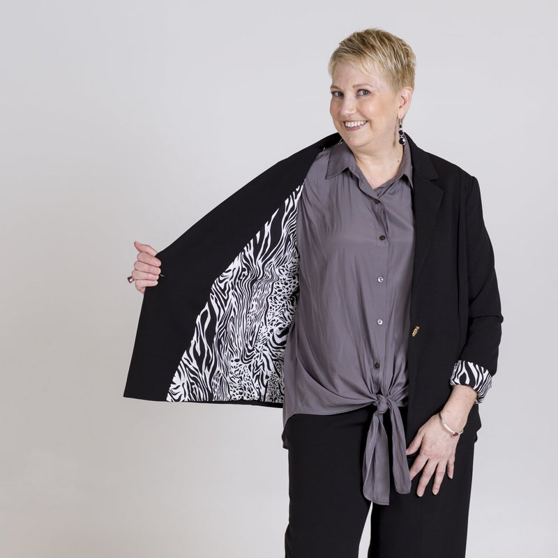 Kerryn blazer black with Cate technical shirt sage. Model is showing the safari print which lines the blazer.
