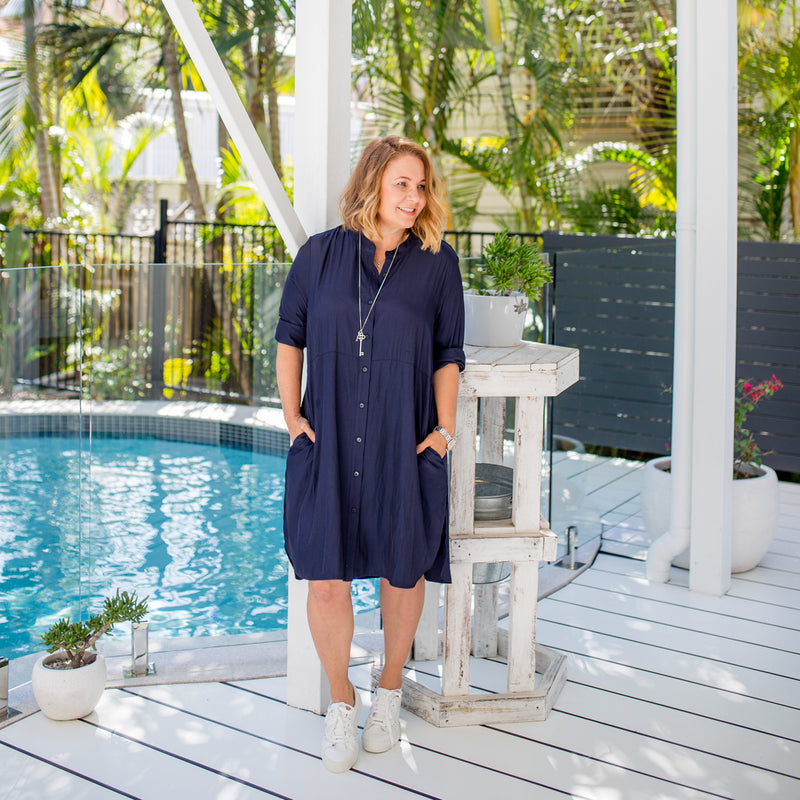 Karen wearing our Danielle technical shirt dress in navy paired with white sneakers