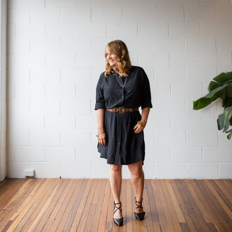 Danielle technical shirt dress in black, styled with a leopard print belt tied around the waist and black strappy heels.