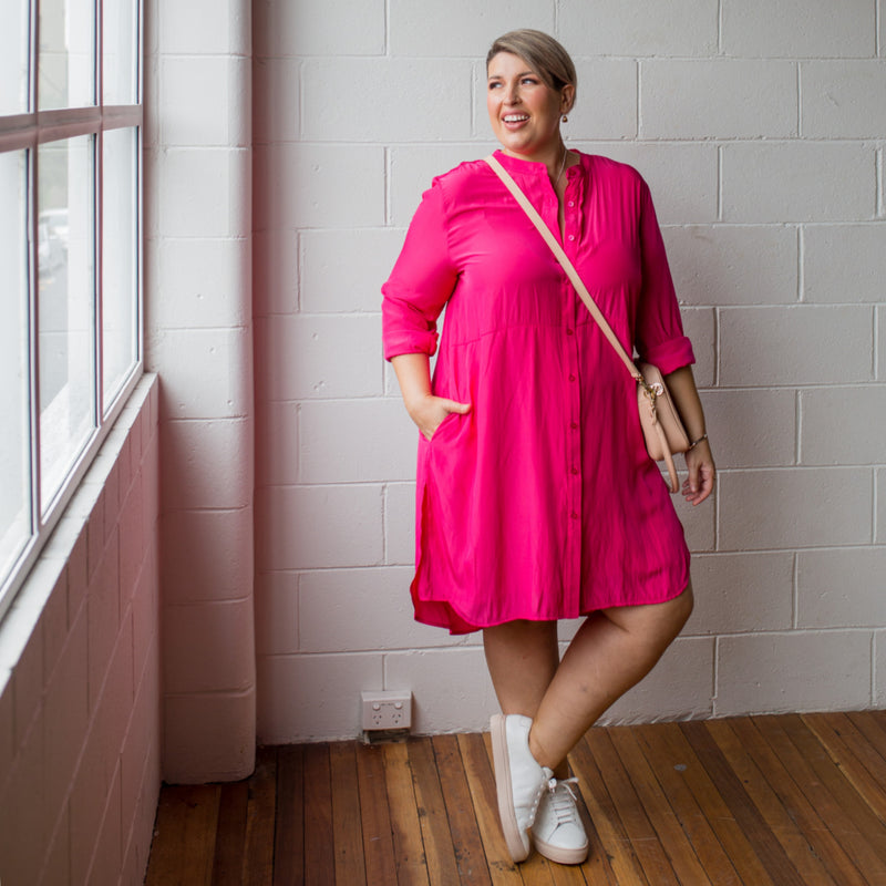 Danielle technical shirt dress raspberry, styled with white sneakers and across-body tan bag.